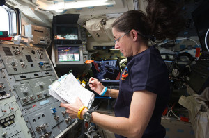 NASA astronaut Nicole Stott, STS-133 mission specialist, reads a procedures checklist on the aft flight deck of space shuttle Discovery while docked with the International Space Station.