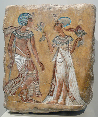 Ancient Egyptian artwork showing a royal couple who wearing scarfs under their headdresses. They are believed to be Akhenaten, an Egyptian Pharaoh and Nefertiti, the Great Royal Wife and Egyptian Queen